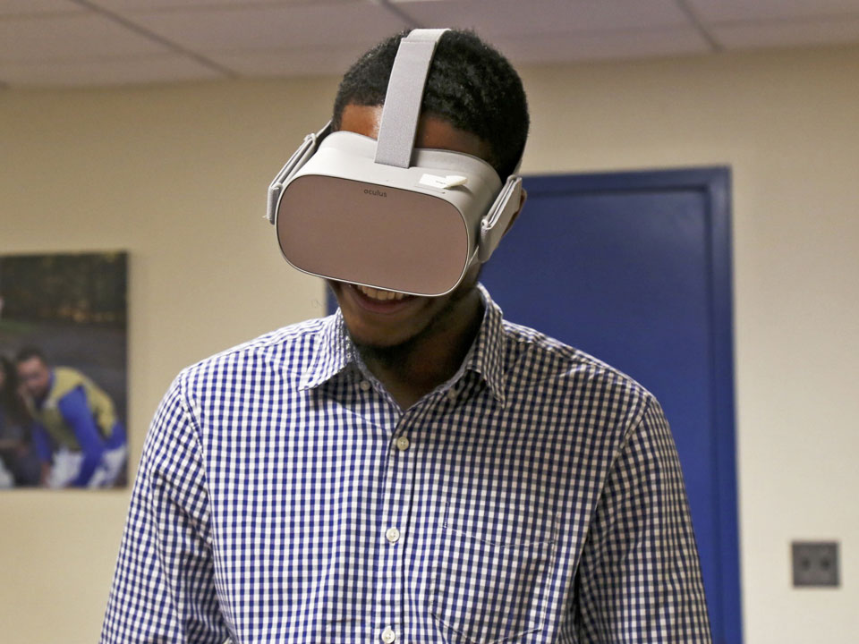 Photo of Lehman Student wearing VR goggles