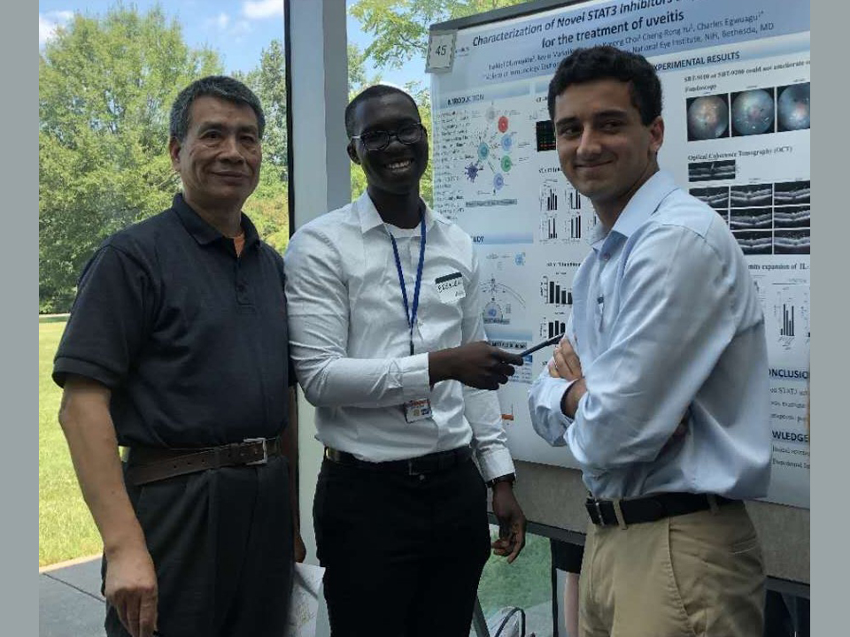 Ezekiel Olumuyide, pictured center, worked with National Institute of Health staff scientist  Dr. Cheng Rong-Yu, left, during an internship last year.